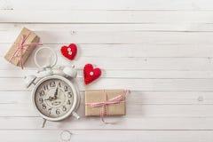 Fondo con la sveglia bianca, i contenitori di regalo ed i cuori rossi sopra Fotografia Stock