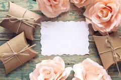 Fondo con la tarjeta de papel en blanco, las cajas de regalo y las rosas en un viejo Imagen de archivo