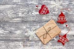Fondo con las decoraciones de la Navidad y el paquete rojos de letras Fotografía de archivo