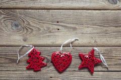 Fondo con las decoraciones rojas de la Navidad en los viejos tableros de madera Imagen de archivo libre de regalías