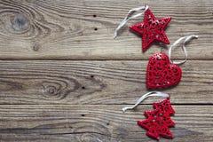 Fondo con las decoraciones rojas de la Navidad en los viejos tableros de madera Imagenes de archivo