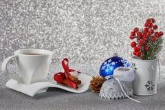 Fondo con las decoraciones, una taza de la Navidad con un platillo, un Ca Imagen de archivo libre de regalías