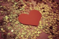 fondo con las estrellas brillantes de oro y el corazón rojo Foto de archivo
