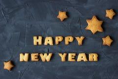 Fondo con las estrellas cocidas del pan de jengibre y Feliz Año Nuevo de las palabras Idea creativa Foto de archivo
