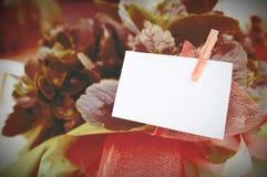 Fondo con las flores y una tarjeta vacía fijada con un perno Espacio vacío de la copia para el texto del redactor fotografía de archivo libre de regalías
