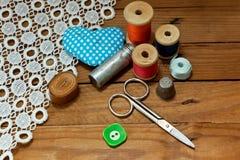 Fondo con las herramientas de costura y el hilo coloreado Fotos de archivo