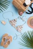 Fondo con las hojas de palma, sombrero de la moda, bikini, chancletas, bolso en un fondo azul en colores pastel ligero, viaje del imagen de archivo libre de regalías