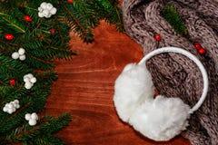 Fondo con las ramas de árbol de navidad, la bufanda y el auricular de la piel Fotos de archivo