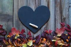 Fondo con le foglie di autunno, il cuore dell'ardesia ed il gesso Fotografie Stock