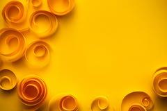 Fondo con le spirali ed i turbinii di carta gialli, arte di carta; concetto della carta anniversario/accogliere Fotografie Stock
