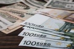 Fondo con los billetes de dólar americanos del dinero y los billetes de banco euro en la tabla Foto de archivo libre de regalías
