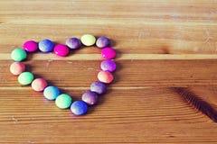 Fondo con los caramelos del color en la forma de un corazón en la tabla de madera en el tono del vintage Imagen de archivo
