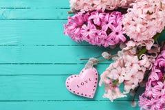 Fondo con los jacintos rosados y corazón decorativo en turq Fotos de archivo