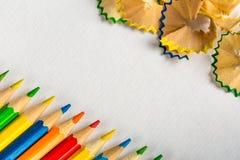 Fondo con los lápices coloreados y los lápices que afilan en el papel Fotos de archivo libres de regalías