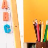 Fondo con los lápices y las letras coloreados Imagen de archivo libre de regalías