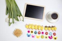 Fondo con los tulipanes blancos y las figuras divertidas de pollos y de flores del fieltro Teléfono móvil amarillo Foto de archivo libre de regalías