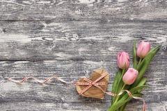 Fondo con los tulipanes rosados y los corazones de madera en tableros grises pl Imágenes de archivo libres de regalías