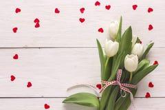 Fondo con los tulipanes y los corazones blancos en los tableros blancos lugar Foto de archivo libre de regalías