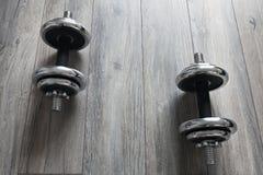 Fondo con pesas de gimnasia en un piso de madera Imagen de archivo libre de regalías