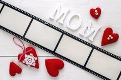 Fondo con un marco bajo la forma de película, corazones y madre Imagen de archivo