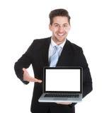Fondo confiado del blanco de Displaying Laptop Over del hombre de negocios fotografía de archivo