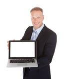 Fondo confiado del blanco de Displaying Laptop Over del hombre de negocios foto de archivo