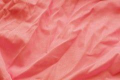 Fondo coralino de un material de materia textil con el modelo de mimbre, primer Contexto del paño Tela arrugada Foco selectivo imagen de archivo libre de regalías
