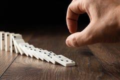 Fondo creativo, mano maschio che spinge i domino bianchi, su un fondo di legno marrone Concetto di effetto di domino, catena immagine stock