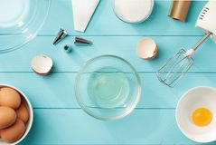 Fondo culinario con le chiare dell'uovo ed i tuorli separati nelle ciotole sulla tavola di legno blu fotografie stock libere da diritti