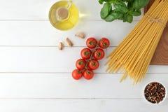 Fondo culinario de las pastas con bucatini seco, albahaca fresca y tomates en la tabla de madera blanca Fotografía de archivo libre de regalías