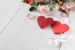 Fondo, cuori e fiori di giorno di S. Valentino su legno bianco Immagine Stock