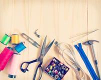 Fondo d'annata con gli strumenti di cucito e nastro adesivo/il corredo di cucito colorati Fotografia Stock