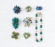 Fondo d'annata dei gioielli Bei fibula, collana ed orecchini luminosi del cristallo di rocca su legno bianco Disposizione piana, Immagini Stock