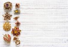 Fondo d'annata dei gioielli Bei fibula ed orecchini luminosi del cristallo di rocca su legno bianco Disposizione piana, vista sup Fotografia Stock