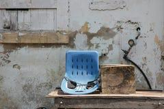 Fondo d'annata della parete con la vecchia sedia blu immagine stock libera da diritti