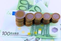 Fondo de billetes de banco y del primer euro de las monedas Imagen de archivo