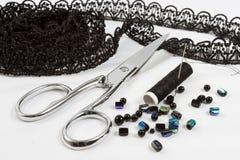 Fondo de costura: tijeras del metal, cuerdas de rosca del negro Fotografía de archivo libre de regalías
