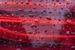 Fondo de cristal rojo del diseño de las tiras con los waterdrops Fotografía de archivo