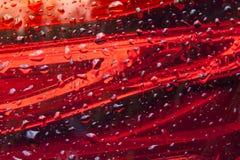 Fondo de cristal rojo del diseño de las tiras con los waterdrops Fotos de archivo