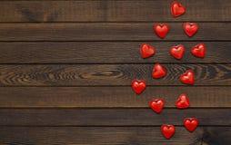 Fondo de día de San Valentín con los corazones rojos en una tabla de madera, visión superior Fondo de madera para el diseño al dí imagenes de archivo