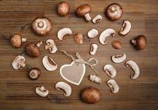 Fondo de Forest Mushrooms y tarjeta del deseo del corazón en la tabla de madera Fotos de archivo libres de regalías