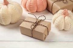 Fondo de Halloween con las cajas de regalos y las calabazas decorativas hechas punto en los tableros blancos Imagen de archivo libre de regalías