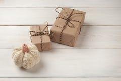 Fondo de Halloween con las cajas de regalos y la calabaza hecha punto decorativa en los tableros blancos Espacio para el texto Imágenes de archivo libres de regalías