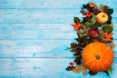 Fondo de la acción de gracias con las hojas y la calabaza en de madera azul Foto de archivo