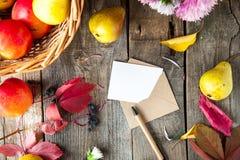 Fondo de la acción de gracias con las frutas, las flores, la tarjeta de felicitación y el sobre estacionales en una tabla de made Imagen de archivo
