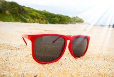 Fondo de la arena con las gafas de sol con el marco rojo Imagen de archivo libre de regalías