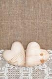 Fondo de la arpillera con el paño de encaje y los corazones de madera Fotos de archivo libres de regalías