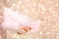 Fondo de la boda con los anillos de oro, la pluma rosada y el li mágico imágenes de archivo libres de regalías