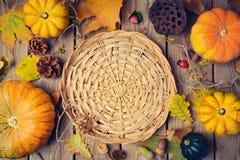 Fondo de la cena de la acción de gracias con la cesta Hojas de la calabaza y de la caída de otoño en la tabla de madera Fotografía de archivo libre de regalías