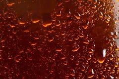 Fondo de la cerveza, descensos que fluyen de la macro sobre el vidrio Imagenes de archivo